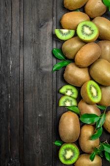Kiwi mûr avec des feuilles sur table rustique noire