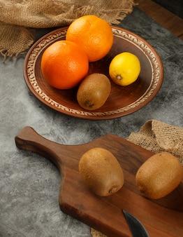 Kiwi, orange et citron dans un fond rustique. vue de dessus.