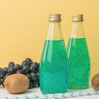 Kiwi, raisins bleus et deux bouteilles de cocktail exotique sur fond jaune. une boisson exotique.