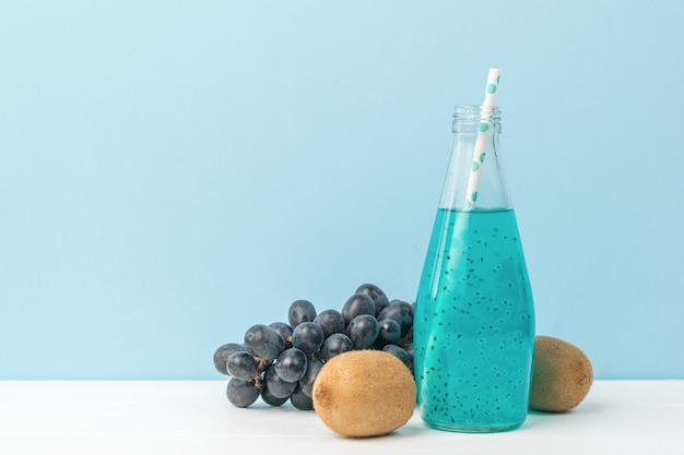 Kiwi, raisins et une bouteille de cocktail bleu sur un tableau blanc sur une surface bleue