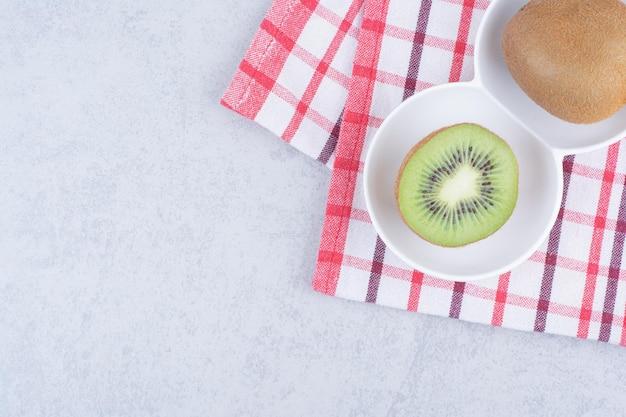 Un kiwi en tranches dans une assiette blanche sur une nappe.