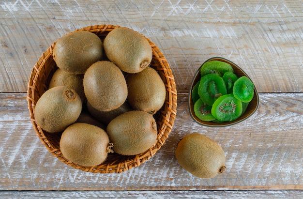 Kiwi avec tranches séchées dans un panier en osier sur table en bois, pose à plat.