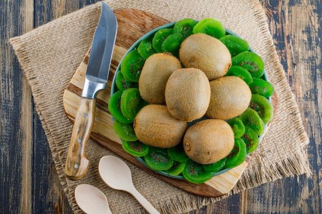 Kiwi avec tranches séchées, planche à découper, couteau, cuillères dans une assiette sur bois et morceau de fond de sac, pose à plat.