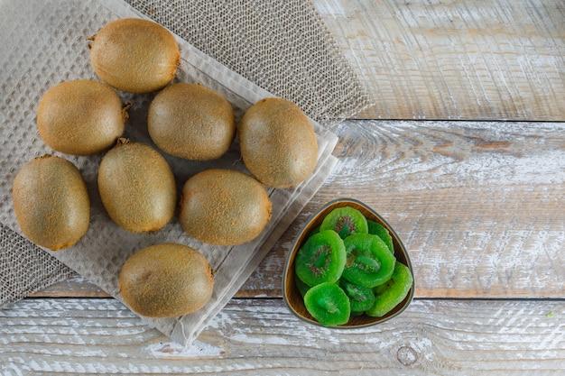 Kiwi avec tranches séchées, torchon de cuisine à plat poser sur table en bois