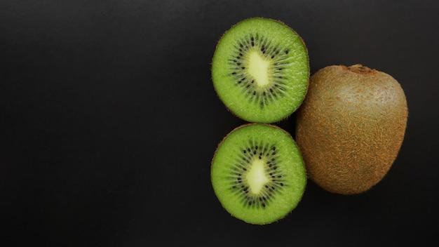 Kiwi vert juteux sur une surface noire, vue du dessus, copiez l'espace