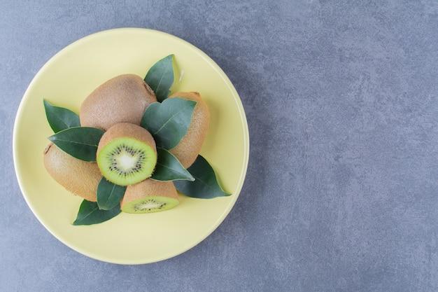 Kiwis entiers et demi sur une assiette sur la surface sombre