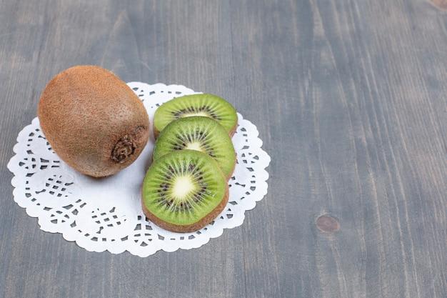 Kiwis mûrs et tranches sur une surface en bois