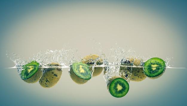 Des kiwis qui tombent dans l'eau et créent des éclaboussures.