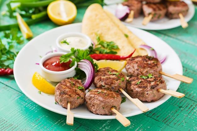 Kofta kebab appétissant (boulettes de viande) avec des tacos de sauce et de tortillas sur une assiette blanche