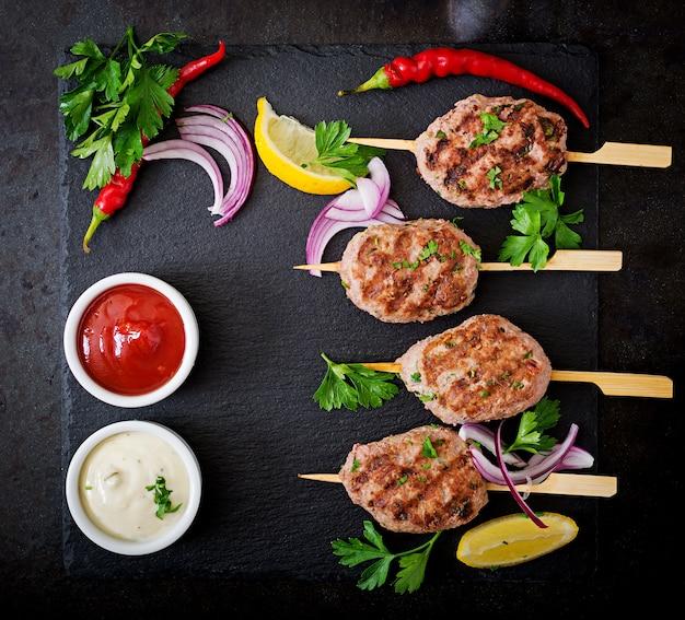 Kofta kebab appétissant (boulettes de viande) avec des tacos de sauce et de tortillas sur fond noir