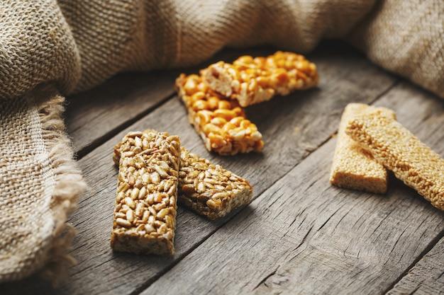 Kozinaki assortis ,, avec toile de jute. style campagnard. délicieuses sucreries à base de graines de tournesol, de sésame et d'arachides, recouvertes d'un glaçage brillant.