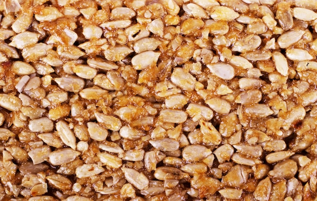 Kozinaki de fèves de cacahuètes dorées et grillées en arrière-plan, texture. prise de vue macro, gros plan.