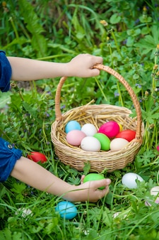 Krashenki oeufs faits maison dans le panier et les mains d'un enfant.