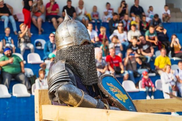 Krasyliv, ukraine. septembre 2019. un homme en costume de chevalier médiéval sur la tribune d'arrière-plan avec les spectateurs_