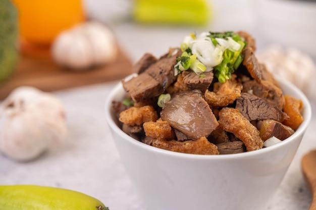 Kuay jab dans une tasse avec des boulettes de viande de porc et des craquelins de porc.