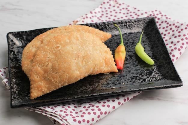 Kue pastel goreng (jalangkote ou karipap) est un casse-croûte feuilleté rempli de carottes en cubes, de pommes de terre et d'œufs. populaire en asie du sud-est sous le nom de curry puff