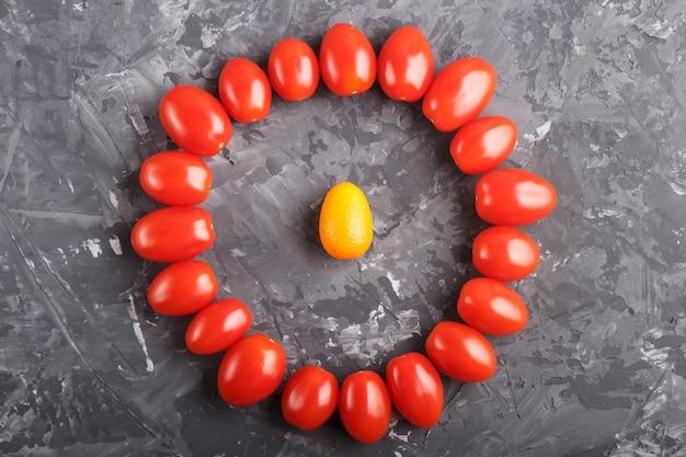 Un kumquat dans un cercle de tomates cerises sur fond noir