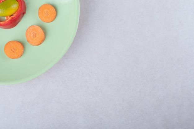 Kumquat, tranches de poivre et carottes tranchées sur plaque sur table en marbre.