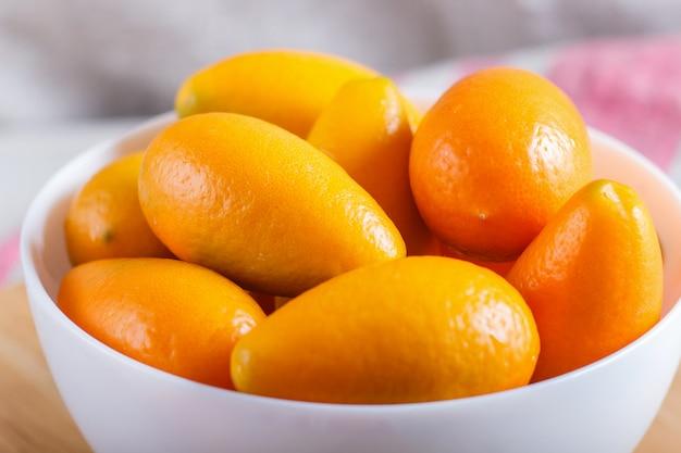 Kumquats dans une assiette blanche sur un bois blanc