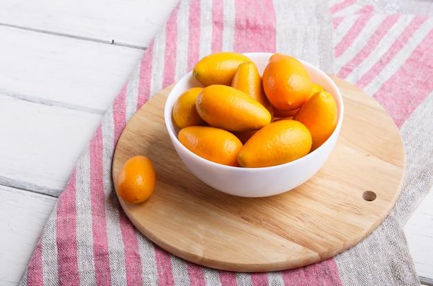 Kumquats dans une assiette blanche sur bois blanc
