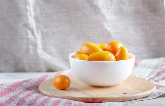 Kumquats dans une assiette blanche sur un plateau de cuisine en bois