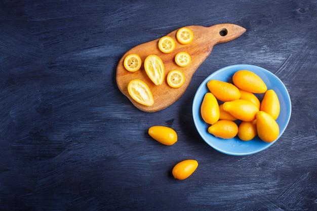 Kumquats dans une assiette bleue sur bois noir