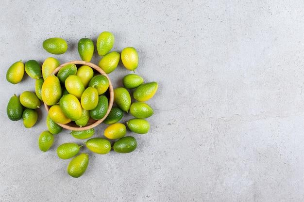 Kumquats dans un bol en bois et éparpillés sur fond de marbre.
