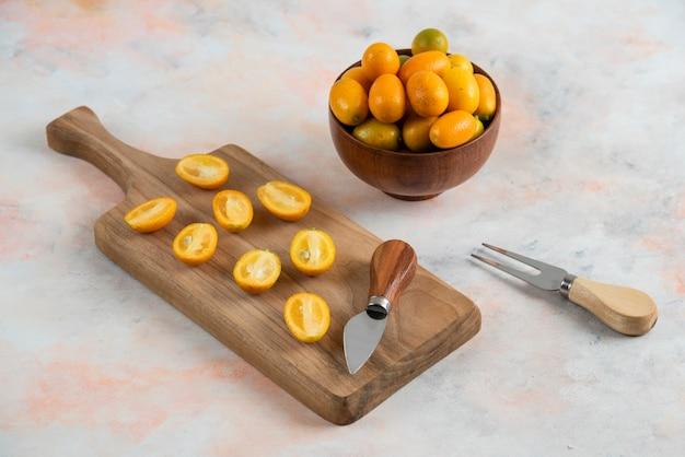 Kumquats entiers dans un bol et la moitié des kumquats coupés sur une planche à découper en bois