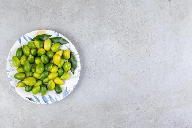 Kumquats et feuilles sur une assiette en fond de marbre.