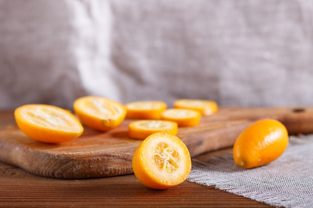 Kumquats tranchés sur un plateau de cuisine en bois