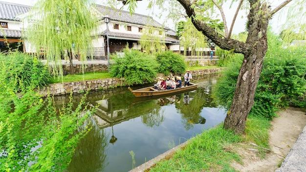 Kurashiki japon - septembre 2016 : les touristes s'amusent avec le bateau à l'ancienne le long du canal de kurashiki dans la ville de kurashiki. la ville conservatrice de la préfecture d'okayama