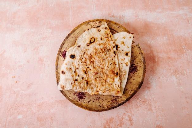 Kutab lavash caucasien avec des épices de sumakh sur un morceau de bois dans un fond texturé.