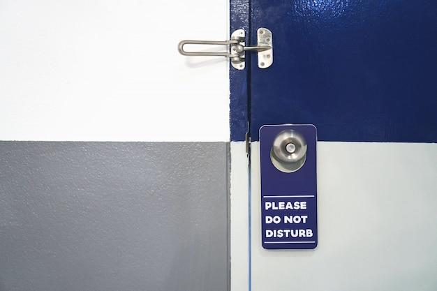 Label s'il vous plaît ne pas déranger blanc avec bleu accrocher à la porte de l'hôtel.