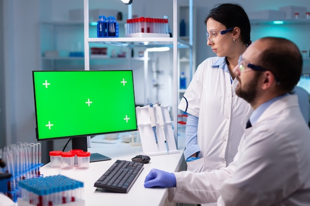 Laboratoire de recherche médicale moderne avec deux scientifiques utilisant un ordinateur avec un écran vert chroma key