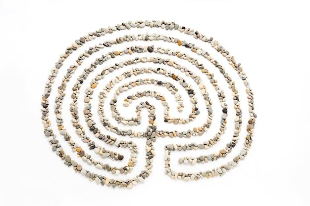 Le labyrinthe sur fond blanc bordé de petites pierres marines.