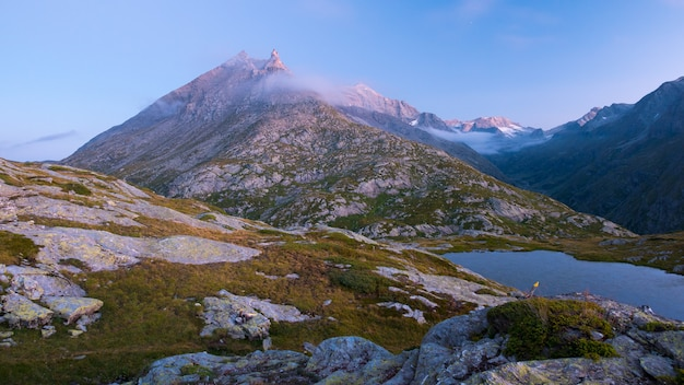 Lac alpin d'altitude dans un pays idyllique avec de majestueux sommets rocheux.