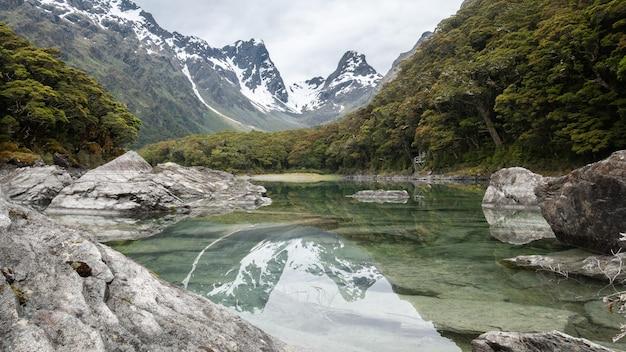 Lac alpin immaculé reflétant l'environnement environnant tourné sur routeburn track nouvelle-zélande