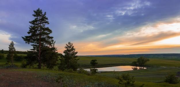 Lac au coucher du soleil dans la forêt parmi des prés verts et des nuages spectaculaires. paysage d'été pittoresque de la nature russe.
