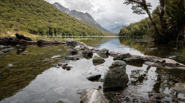 Lac au milieu de la forêt reflétant son environnement tourné sur routeburn track nouvelle-zélande