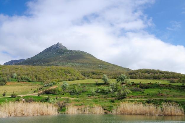 Lac aux eaux boueuses et roseaux en croissance, ciel bleu et petit village parmi les montagnes