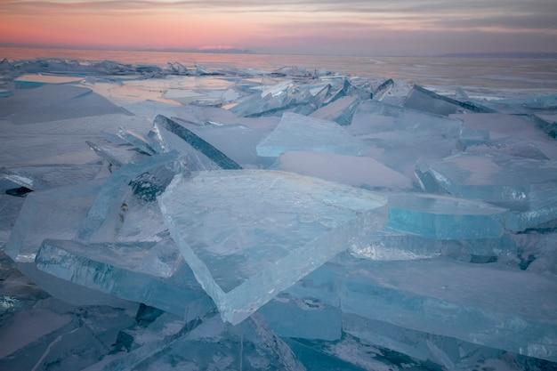 Lac baïkal au coucher du soleil, tout est couvert de glace et de neige, de glace bleu clair épaisse.