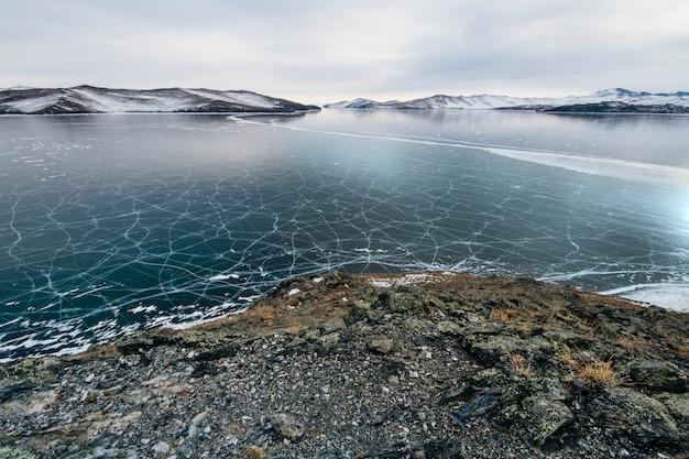 Le lac baïkal est couvert de glace et de neige, de froid intense et de givre, de glace bleu clair épaisse.
