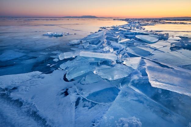 Le lac baïkal est recouvert de glace et de neige, d'un froid intense et d'une glace bleu clair épaisse.