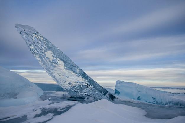 Le lac baïkal est recouvert de glace et de neige, de glace bleu clair épaisse et froide. des glaçons pendent des rochers