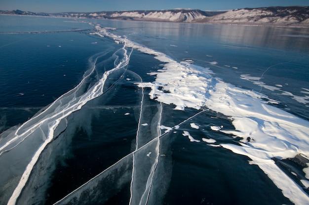 Le lac baïkal est recouvert de glace et de neige, de glace bleu clair épaisse et froide.