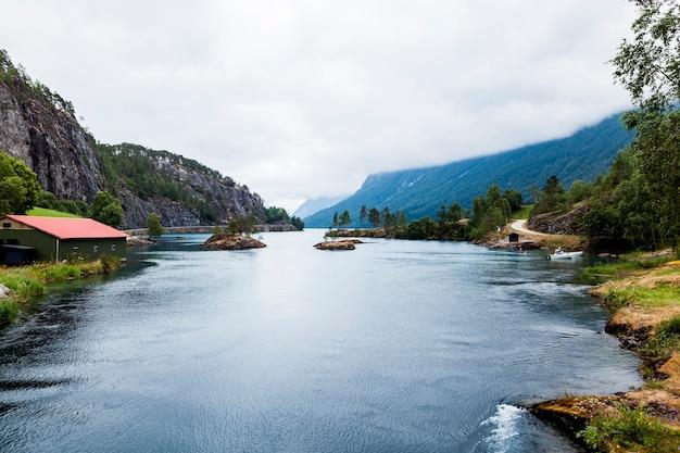 Lac bleu idyllique avec la montagne brumeuse