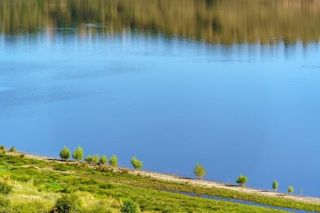 Lac bleu avec petits arbres sur le rivage et reflets verts des arbres. copiez l'espace et l'arrière-plan. espagne.