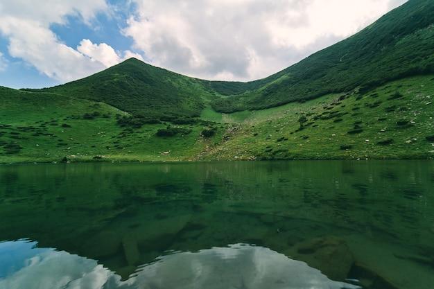 Lac clair sur fond de montagnes vertes et de ciel bleu par temps ensoleillé d'été. tourisme, loisirs, escalade.