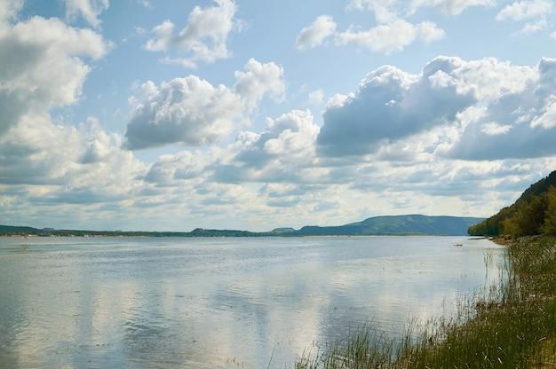 Lac avec une côte herbeuse et des nuages dans le ciel bleu.