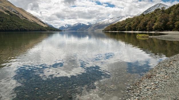 Lac cristallin entouré de forêt et de montagnes tourné à mavora lakes nouvelle-zélande